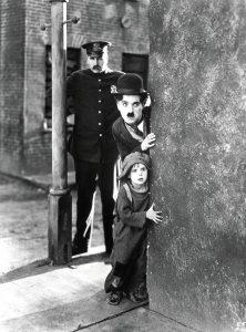 Police officer, Charlie, and the Kid peeking around the corner