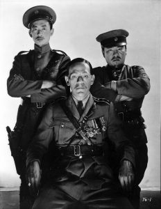 Boris Karloff as General Wu Yen Fang, with his right-hand man Mr. Cheng to one side, and the man who accepted a bribe on the other