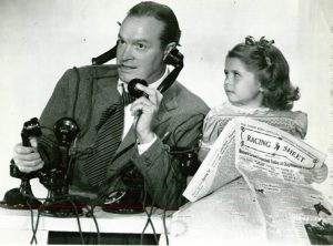 Publicity photo for Sorrowful Jones with Bob Hope reading a racing sheet while Miss Marker watches