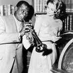 "Louis ""Satchmo"" Armstrong blowing his trumpet while Grace Kelly looks on in a photograph from the set of the MGM motion picture ""High Society."" Louis Armstrong and Grace Kelly both featured along with Bing Crosby, Frank Sinatra and Celeste Holm."