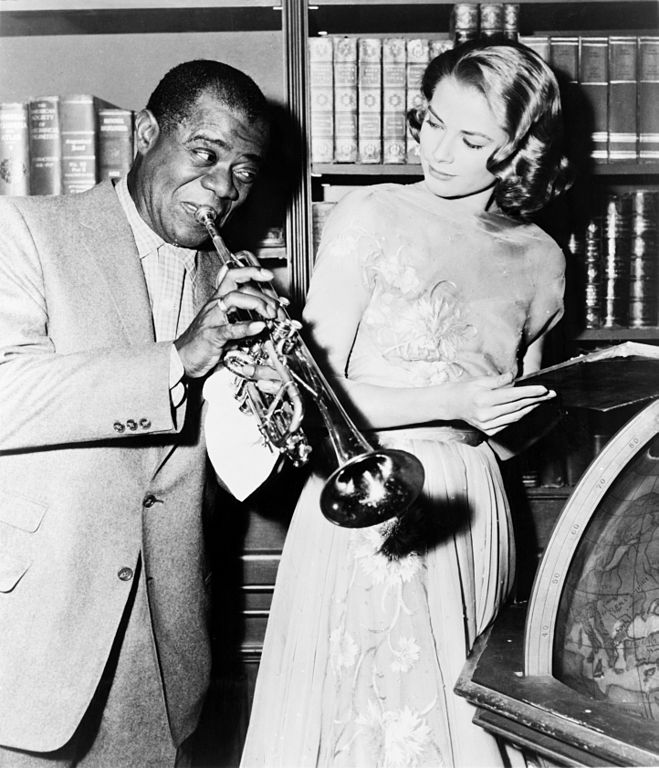 """Louis """"Satchmo"""" Armstrong blowing his trumpet while Grace Kelly looks on in a photograph from the set of the MGM motion picture """"High Society."""" Louis Armstrong and Grace Kelly both featured along with Bing Crosby, Frank Sinatra and Celeste Holm."""