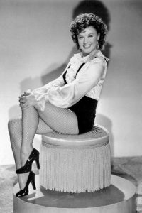 Ginger Rogers as Roxie Hart sitting on a chair in a publicity photo