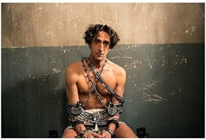 Adrien Brody as Houdini, chained in a cell