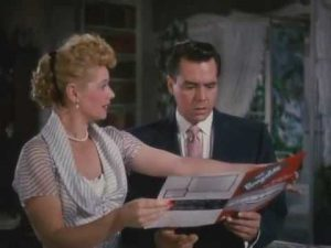 Lucy showing Desi a trailer brochure