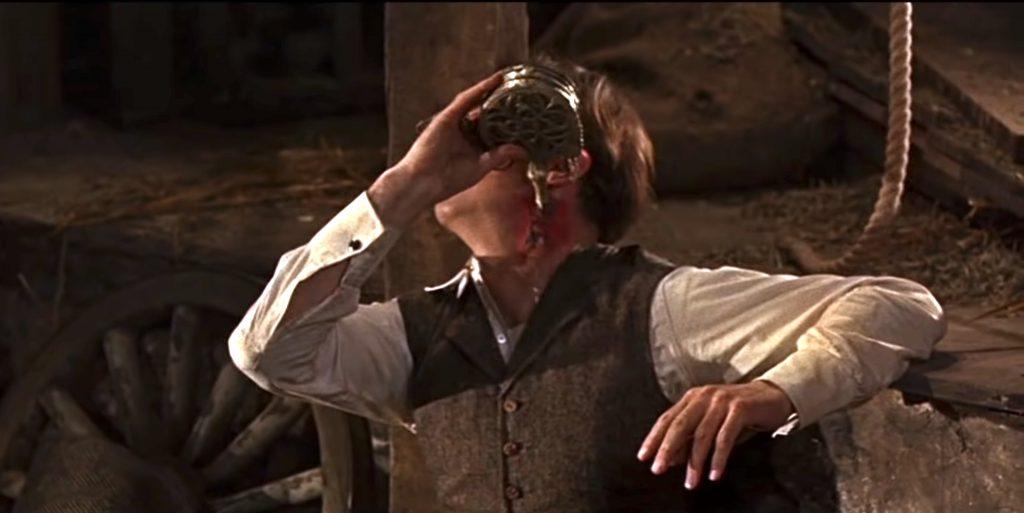 Van Helsing applying holy water to his vampire bite