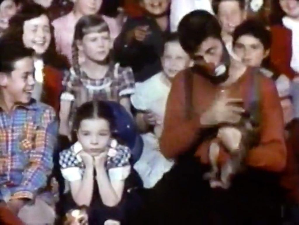 """Jericho (Jerry Lewis) a the orphan's benefit, """"monkeying"""" around with a small monkey"""