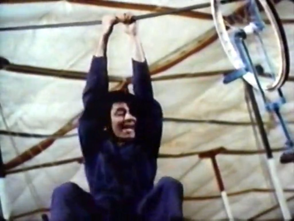 Jerry Lewis clowning around on the high wire, with a tricycle